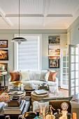 Verschiedene Utensilien auf Tischen und Sofa mit Kissen unter weisser Holzpaneeldecke in traditionellem Wohnzimmer