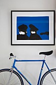 Contemporary blue and black artwork and racing bike in matching colours against white wall