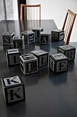 Several alphabet blocks on dark table top and fifties-style chairs