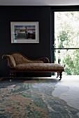 Antike Chaise Longue auf Rollen vor dunkel getönter Wand mit gerahmter Fotografie neben Schiebefenstertür; gemusterter Teppich mit Natursteinoptik