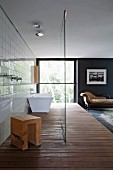 Bedroom with open-plan bathroom on wooden platform; bathtub, wooden stool and rain shower behind glass screen, large window and antique recamier in background