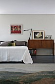 60s sideboard, contemporary art and photographs next to bed with bedspread