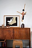 Framed picture (illustration) and wooden sculptures on 60s sideboard