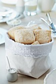Bread bag decorated with lace trim on breakfast table set in white