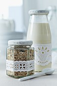 Milk and muesli for breakfast on the go in screw-top jars decorated with lace ribbon