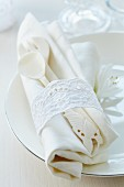 Napkin ring made from lace trim around ornate cutlery & linen napkin on plate