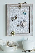 Crocheted doily in picture frame used as jewellery rack