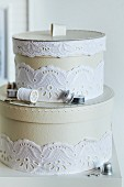 Round storage boxes for sewing kit decorated with white lace ribbon
