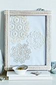 Collage of crocheted doilies in picture frame decorated with lace trim