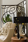 Black glass vase of flowers and table lamp with black lampshade on side table in front of pale armchair and modern, wrought iron screen