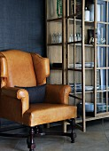 Light brown leather armchair next to display cabinet with open door against dark blue wall