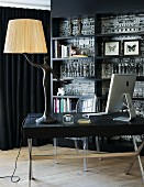 Table lamp with human figurine as base and computer on table in front of Ghost chair and black fitted shelving
