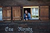 Frau mit Kind am Fenster eines Holzhauses