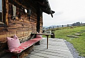 Rustic bench in front of Alpine cabin
