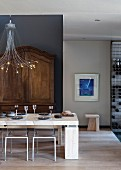 Set, modern dining table below designer pendant lamp in front of antique cupboard against grey wall