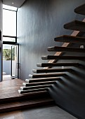 Floating stair treads protruding from wall in minimalist stairwell with open terrace door