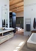 Elegantes Bad mit raumhohem Durchgang und Blick in Schlafzimmer mit Ankleide