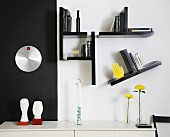 Sideboard against black and white wall with small shelves arranged asymmetrically