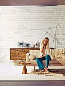 Blonde woman sitting on sofa in front of retro, leopard-patterned sideboard