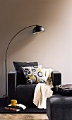 Arc lamp next to black armchair with scatter cushions