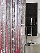 Bead curtain in various colours; black leather bar stools in background