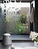 Bathroom with dark grey tiles and shower area in front of glass wall with view into planted courtyard