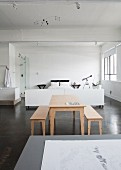 Pale wooden table and benches on grey concrete floor in front of white sleeping area in loft-style interior