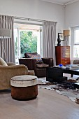 Round pouffe and various armchairs around coffee table on cowhide rug in living room