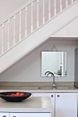 Island unit in front of kitchen counter in niche below staircase with white-painted wooden balustrade