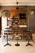 Vintage barstools at counter with glass-fronted drawers in open-plan, fitted kitchen with pendant lamps with lampshades made from stylised leaves
