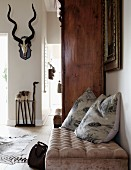 Scatter cushions on ottoman next to antique cupboard; hunting trophy on wall in background