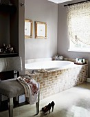 Upholstered chair next to bathtub with tiled side in pleasant bathroom
