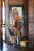 Hats and bags on vintage, metal coat stand against exposed brick walls in niche in hallway
