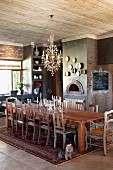 Long dining table and various chairs on Oriental rug below chandelier in rustic dining room with fireplace