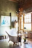 Free-standing vintage bathtub below chandelier in rustic bathroom with concrete floor