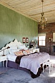 Double bed with upholstered, Baroque-style headboard against green wall in rustic bedroom with brick wall and wooden ceiling