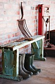 Vintage gardening tool on rustic wooden bench over wellington boots against brick wall