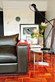 Partially visible leather couch and retro lamp on side table on mosaic parquet floor