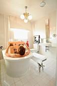 Man bathing in free-standing bathtub in modern, white bathroom