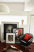 Black, leather swivel chair in front of collection of pictures and portrait of Obama leaning on wall