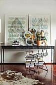 Kuhfell auf Parkettboden und Metallstuhl vor postmodernem Wandtisch mit Bildern und Kunstobjekten