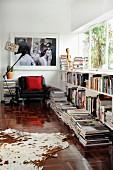 Kuhfell und Bücherstapel auf Boden vor halbhohem Regal unter Fensterband, im Hintergrund Sessel & grossformatiges Foto an Wand