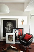 Black, leather swivel chair in front of collection of pictures and portrait of Obama