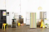 Various fashionable fridges, drinks and a yellow stool