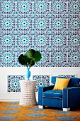 Eye-catching wall decor with pattern similar to oversized Moroccan tiles, colour-coordinated armchair and side table