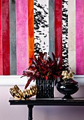 Wall decor with fabric wallpaper; stripes of colour and animal print pattern behind gold and black ornaments on console table