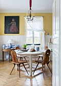 Traditional Bavarian board chairs at round, white dining table and collection of blue and white china on console table below old oil painting