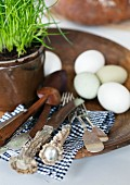 Hand-carved salad servers and old silver cutlery with flat handles and horn handles on black and white gingham napkin; eggs and potted chives on stoneware plate