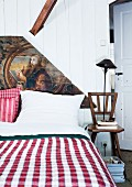Piece of old wooden ceiling from demolished Baroque church used as artistic headboard of double bed with rustic, gingham bedspread and board chair used as bedside table