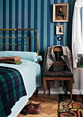 Period brass bedstead and Biedermeier chair against blue striped wallpaper